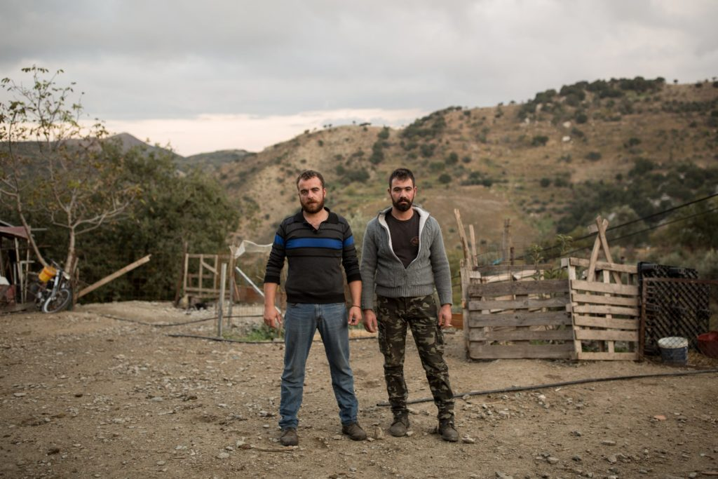 Kostas and Andreas pose next to their barn, in the village of Anogeia.