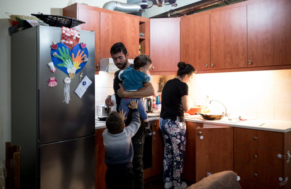 Kostis taking care of the children, while his wife Iro prepares dinner in their home.