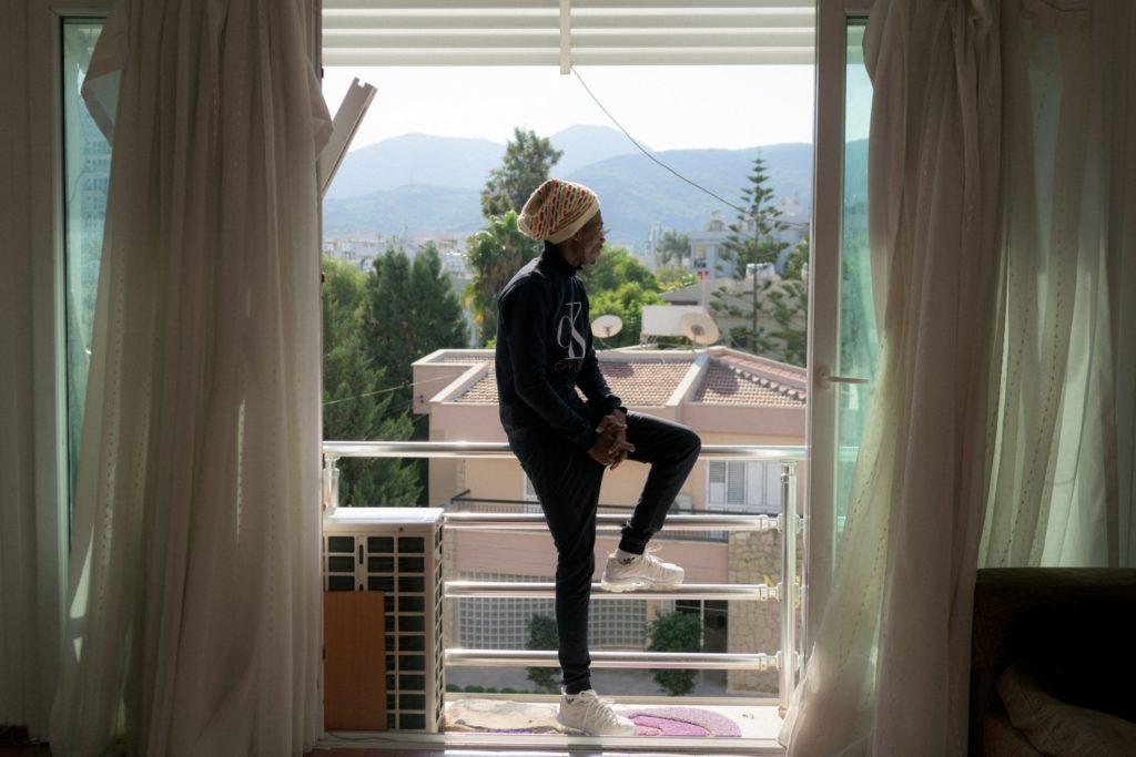 Freddie (25), ein Designer aus Kinshasa, schaut vom Balkon der Wohnung in Girne/Kyrenia, wo er sich derzeit aufhält, die Straße hinunter, während er einige Freunde besucht.