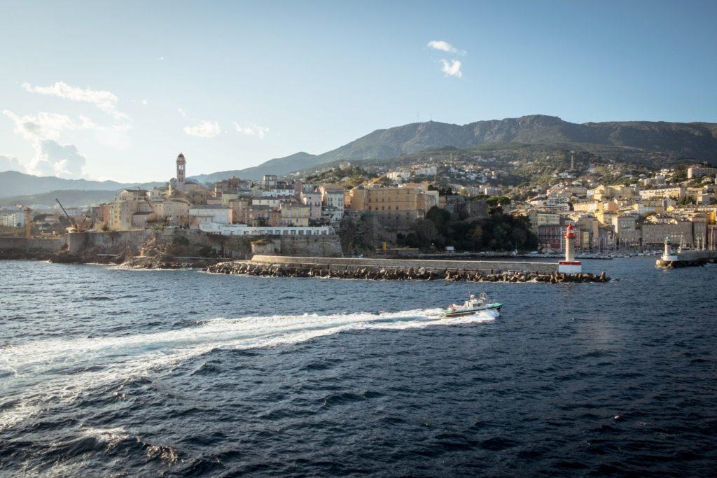 Die Altstadt von Bastia von einem Schiff aus gesehen, welches gerade den Hafen der Stadt verlässt. Zusammen mit der Hauptstadt Ajaccio ist Bastia eine der größten Städte Korsikas. Diese Mittelmeerinsel, strategisch zwischen Italien und Frankreich gelegen, wird von etwa 330.000 Menschen bewohnt. Die Bevölkerungsdichte Korsikas beträgt 37,9 Einwohner pro km², nur ein Drittel des französischen Durchschnitts.