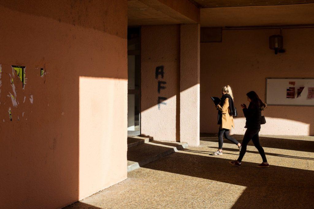"""Studenten laufen an den Graffiti für die Unabhängigkeitsbewegung im Universitätsgebäude in Corte vorbei. APP steht für """"A Francia fora"""" (""""Frankreich verschwinde"""")."""